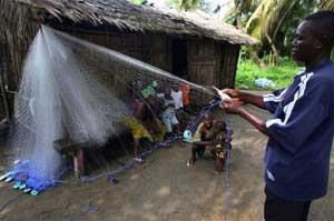 Waibite Amazi, a fisherman in Nigeria's troubled oil-rich delta region, spreads out his net outside his homestead, Nigeria. Farming and fishing is the main source of livelihood for the impoverished, rural population here. Courtesy: Dulue Mbachu/IRIN