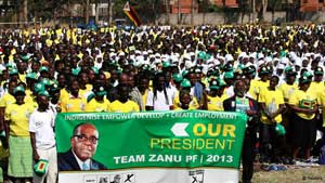 Supporters cheer Zimbabwean President Robert Mugabe as he arrives to launch his ruling ZANU PF party's election manifesto in the capital Harare July 5, 2013.