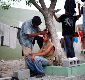A man receives a haircut in mid-April at Casa del Migrante in Reynosa, Mexico. The shelter provides housing, food, clothing and medical care to people who are planning to cross the border, and to those who have been deported from the United States. Pope Francis called for greater international cooperation to improve conditions for the world's rising numbers of migrants. (CNS/Reuters)