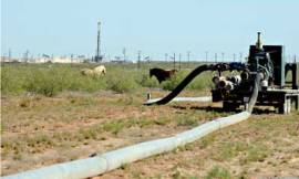 Large hoses run from hydraulic fracturing drill sites in Midland, Texas. Fracking uses huge amounts water to free oil and natural gas trapped deep in underground rocks. With fresh water not as plentiful, companies have been looking for ways to recycle their waste. Photograph: Pat Sullivan/AP