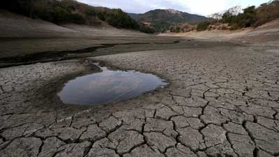 "Small pool of water is surrounded by cracked earth at the Almaden Reservoir (28 January 2014) Farmers said the announcement was ""a terrible blow"""
