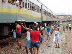 Informal vendors sell food and drinks to passengers on the Carajás Railroad at Alto Alegre do Pindaré, in the northwest of the Brazilian state of Maranhão. This source of income will disappear when the trains are modernised and their windows sealed shut. Credit: Mario Osava/IPS