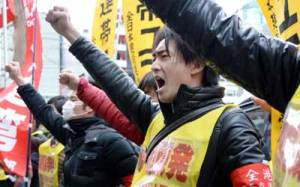 Fukushima nuclear workers and their supporters shouts slogans as they raise their fists in front of the headquarters of Tokyo Electric Power Company (TEPCO), operator of the tsunami-battered Fukushima Daiichi nuclear power plant, during a rally in Tokyo on March 14, 2014.Toru Yamanaka/AFP/Getty Images
