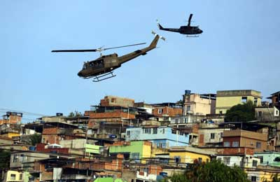 Police helicopters fly over the Maré favela during it's occupation in Rio de Janeiro, Brazil, Sunday, March 30, 2014. (AP Photo/Leo Correa)