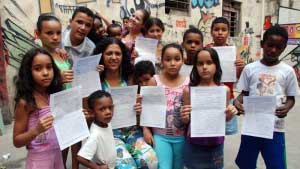 Nete Araujo with children, holding petitions signed by parishioners from England & Wales. www.cafod.org.uk/Campaign/Take-action-today/World-Cup-Brazil-Action