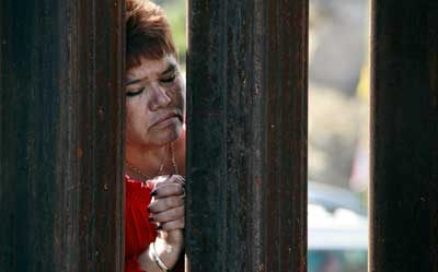 A woman in Mexico peers through the slats of the border fence as a group of U.S. bishops celebrates Mass Tuesday in Nogales, Ariz.