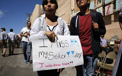 Fatima Rojas, 13, holds a sign with a plea for her sister, who she said has been held at a U.S. facility in Elroy, Ariz., for months, at a news conference held by a visiting group of U.S. bishops Tuesday in Nogales, Ariz