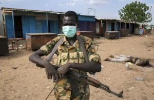 A rebel fighter wears a mask near a body in front of a mosque where people were massacred in Bentiu, South Sudan, April 20. Rebels slaughtered hundreds of civilians when they seized the South Sudan oil hub of Bentiu, hunting down men, women and children who had sought refuge in a hospital, mosque and Catholic church, the United Nations said.