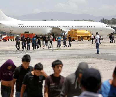 Guatemalan migrants land in Guatemala City July 10 after being deported from the United States. The flight carried 126 men and women. A growing wave of families and unaccompanied minors are fleeing Central America because of an increase in drug and gang-related crimes. (CNS/Reuters)