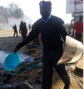A police officer puts out fire lit by traders at Jomo Kenyatta road in Kisumu town to protest demolition of their stalls by county government. PHOTO | ELVIS ONDIEKI | NATION MEDIA GROUP