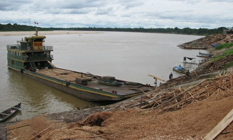 A barge being loaded with freshly cut planks. Photograph: Dan Collyns