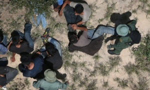 Border patrol agents take men into custody. Photograph: John Moore/Getty Images