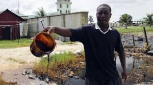 A villager shows a bucket of of crude oil spill at the banks of a river, after a Shell pipeline leaked, in the Oloma community in Nigeria's delta region on 27 November 2014. The local fishing community in Nigeria's delta region have been hardest hit by recent oil spills