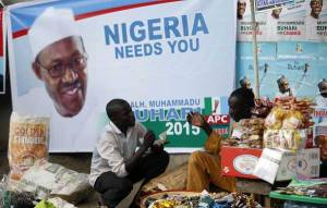 Vendors sell their wares near an election poster of former Nigerian military ruler Muhammadu Buhari before the start of the All Progressives Congress (APC) party convention in Lagos in this December 10, 2014 file photo. (Akintunde Akinleye/Reuters)