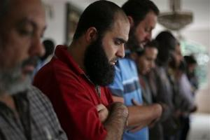 In this May 15, 2015 photo, Syrian refugee Abdulhannan Mouhammed, second from left, attends Friday prayer at a mosque in Sao Paulo, Brazil. Two years after the Syrian civil war broke out, Brazil adopted measures that made it easier for Syrians to be granted refugee status. (AP Photo/Andre Penner)