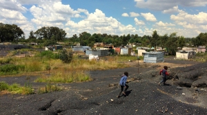 Children at play near the illegal settlements built on a former coal mine [Victoria Schneider/Al Jazeera]