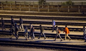 Migrants walk along railway tracks at the Eurotunnel terminal on 28 July. Photograph: Philippe Huguen/AFP/Getty Images
