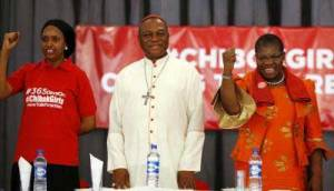 Nigerian Cardinal John Olorunfemi Onaiyekan, center, stands between leaders of the