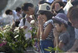 People pray at a memorial in Hiroshima, Japan, Aug. 6, to commemorate the victims of the atomic bombing of the city by the United States in 1945. Delegation members from the World Council of Churches, in Hiroshima for the commemoration, said they would return home to build a movement to rid the world of nuclear weapons. (CNS photo/Paul Jeffrey)