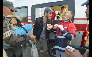 Hungarian volunteers share conversation, Sept. 24, as they give coffee to refugees passing through Hegyeshalom, Hungary, on the way to Austria. (CNS photo/Paul Jeffrey)