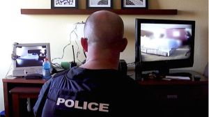 An officer with the Alexandria, Virginia, Police Department monitors an undercover sting operation in a hotel room during Operation Cross Country.Image copyrightFBI