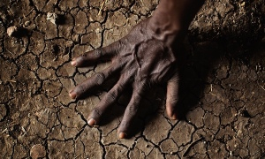 A man in South Sudan's conflict-ridden Upper Nile state places his hand on parched soil. Restricted access to areas affected by fighting has raised fears of a possible famine. Photograph: Julien Behal/PA
